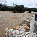 写真: 増水した川と積まれた土嚢